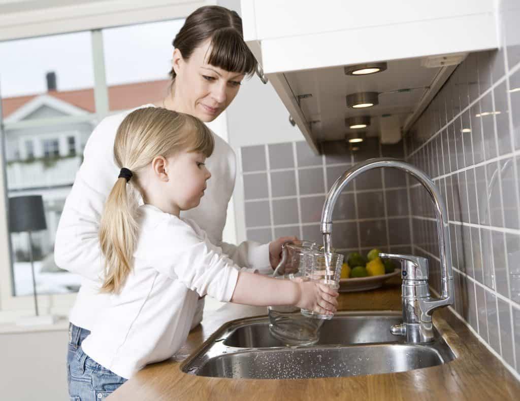 Mãe e filha na cozinha utilizando a melhor Torneira Elétrica