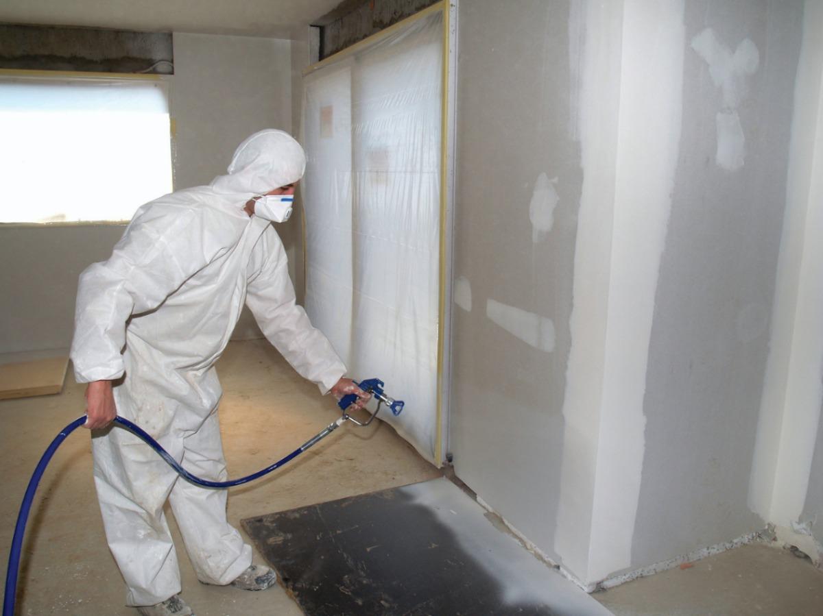 operador equipado e coberto utilizando a melhor maquina de pintura airless para pintar paredes internas