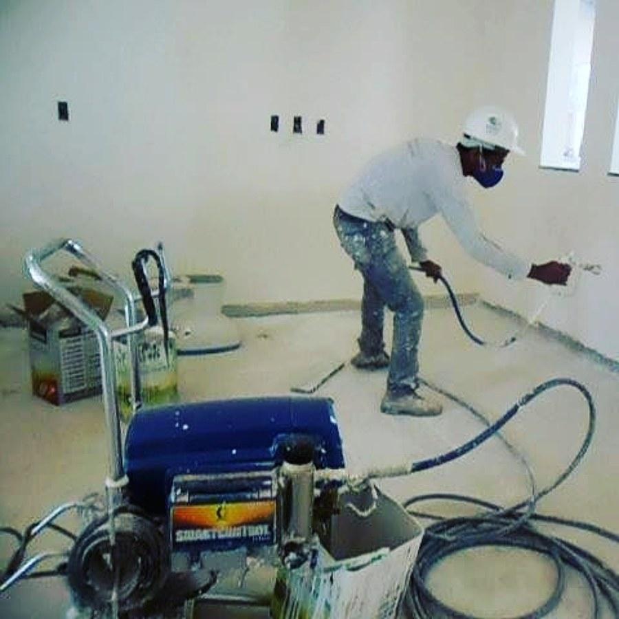 homem usando máquina de pintura airless em parede interna