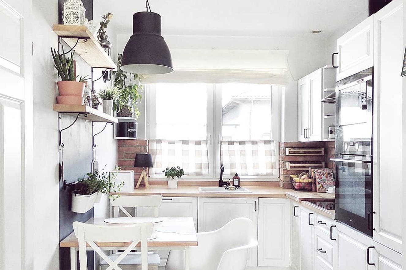 Cozinha escandinava utilizando o ferro fundido em prateleiras, puxadores e luminárias junto a bancadas de madeira clara e gabinetes brancos.