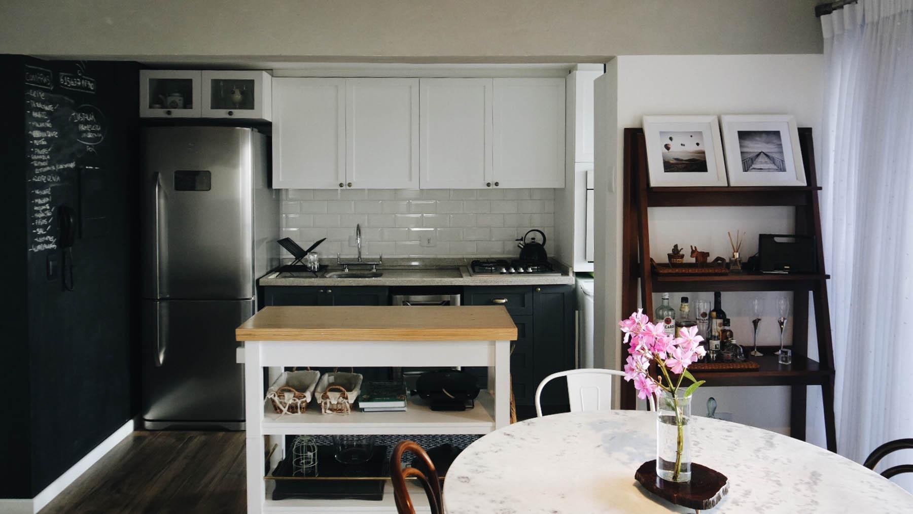 Cozinha escandinava com parede lousa e ilha em madeira, mesa com cadeiras diferentes e tampo de mármore.