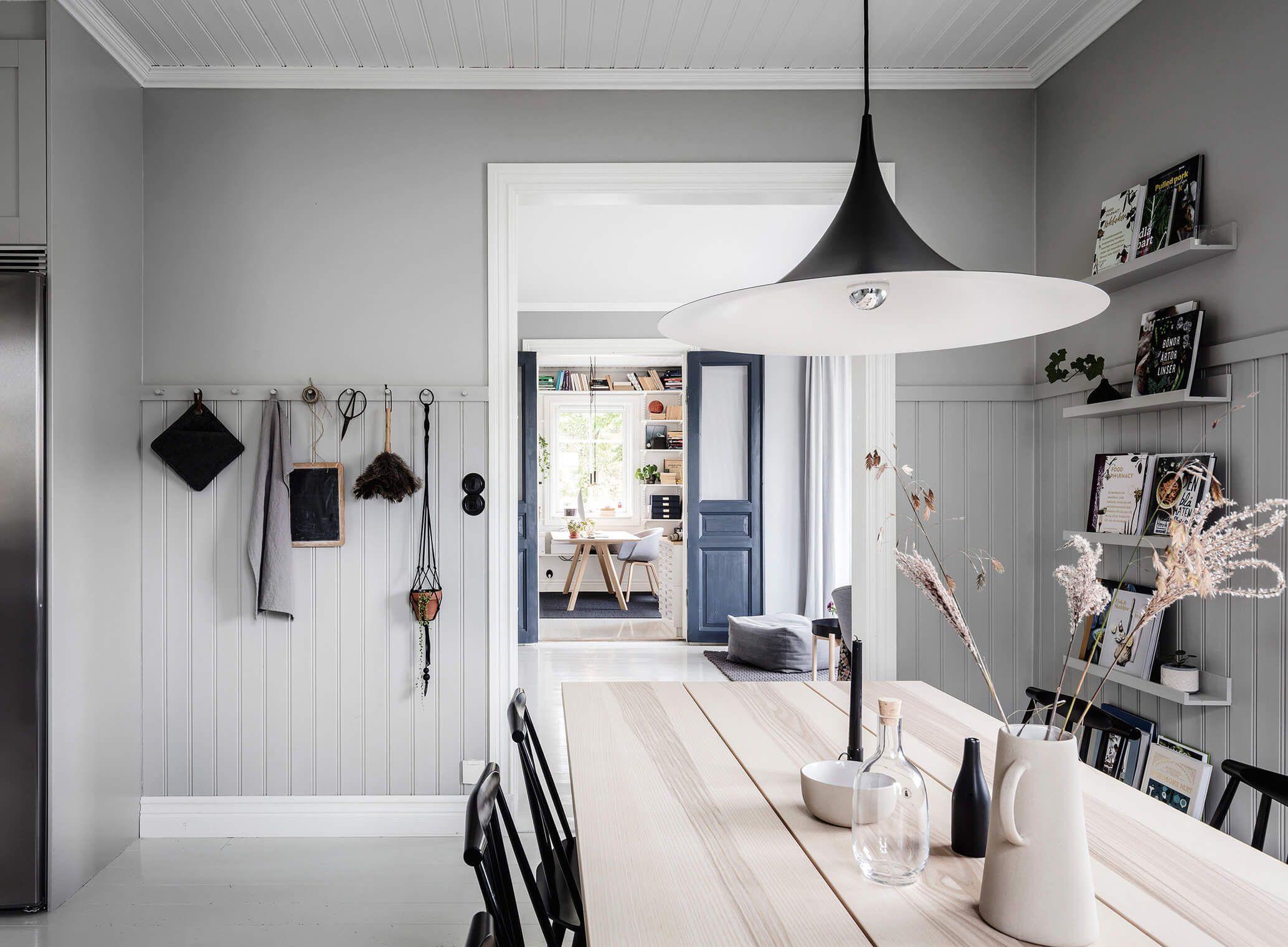 Cozinha escandinava com painel de madeira nas predes e no teto de tons claros pontuada com cadeiras e luminária preta.