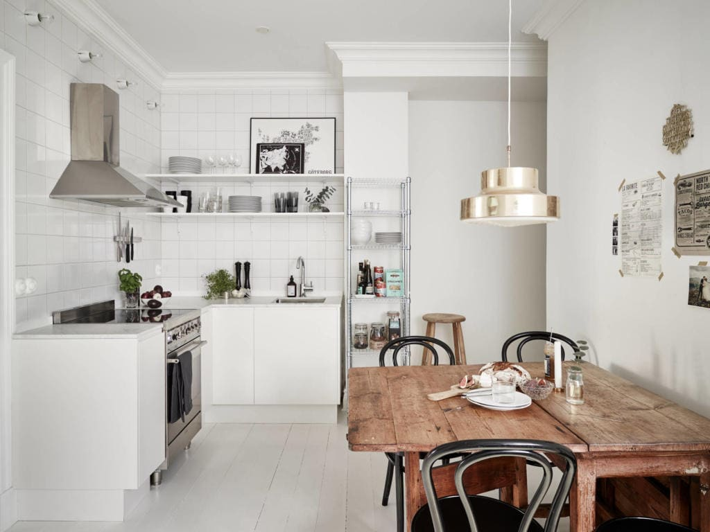 Cozinha escandinava com mesa de madeira rústica incorporada aos azulejos brancos e piso de cerâmica.