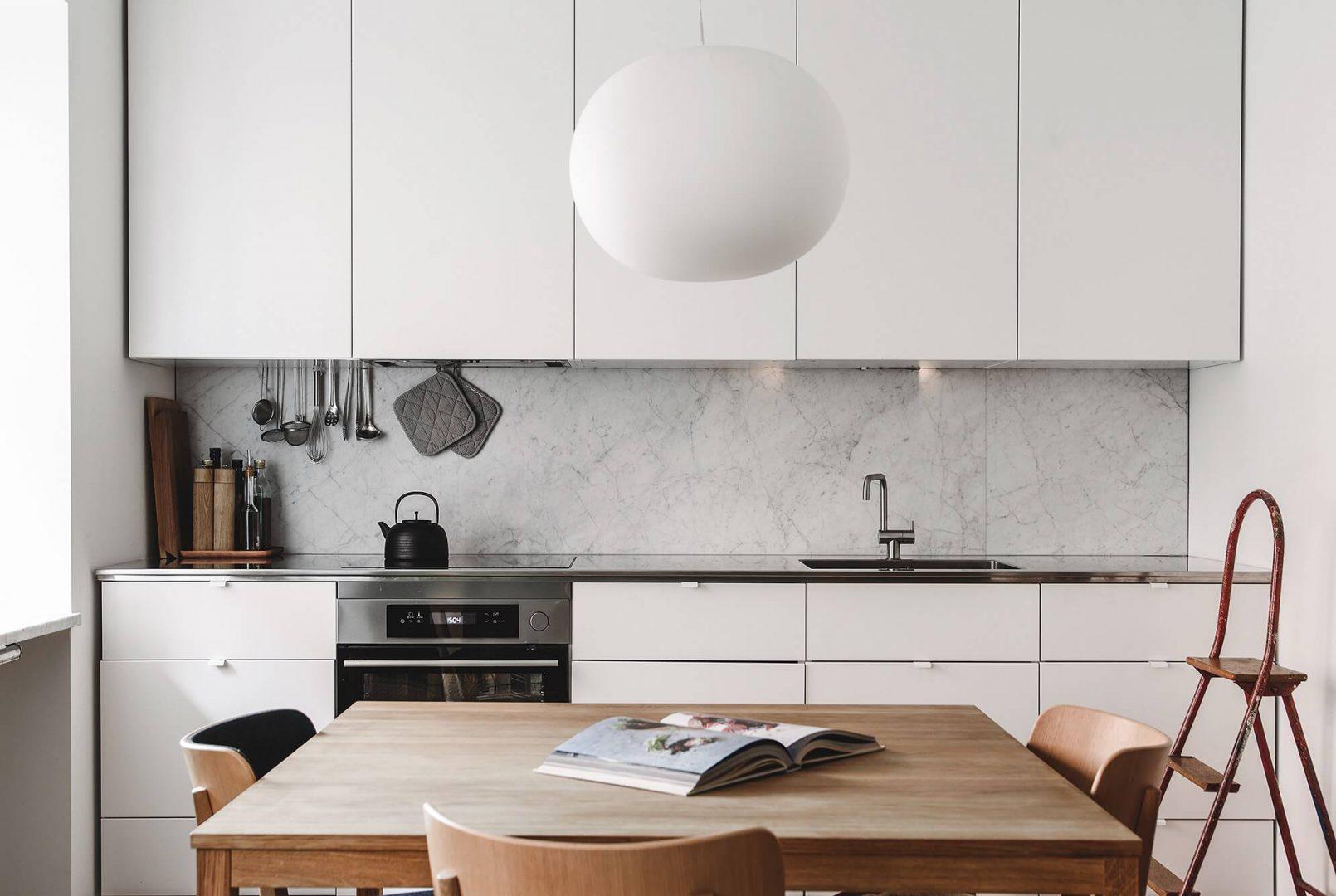 O mármore misturado à madeira e o branco dos armários se misturam nessa cozinha escandinava.