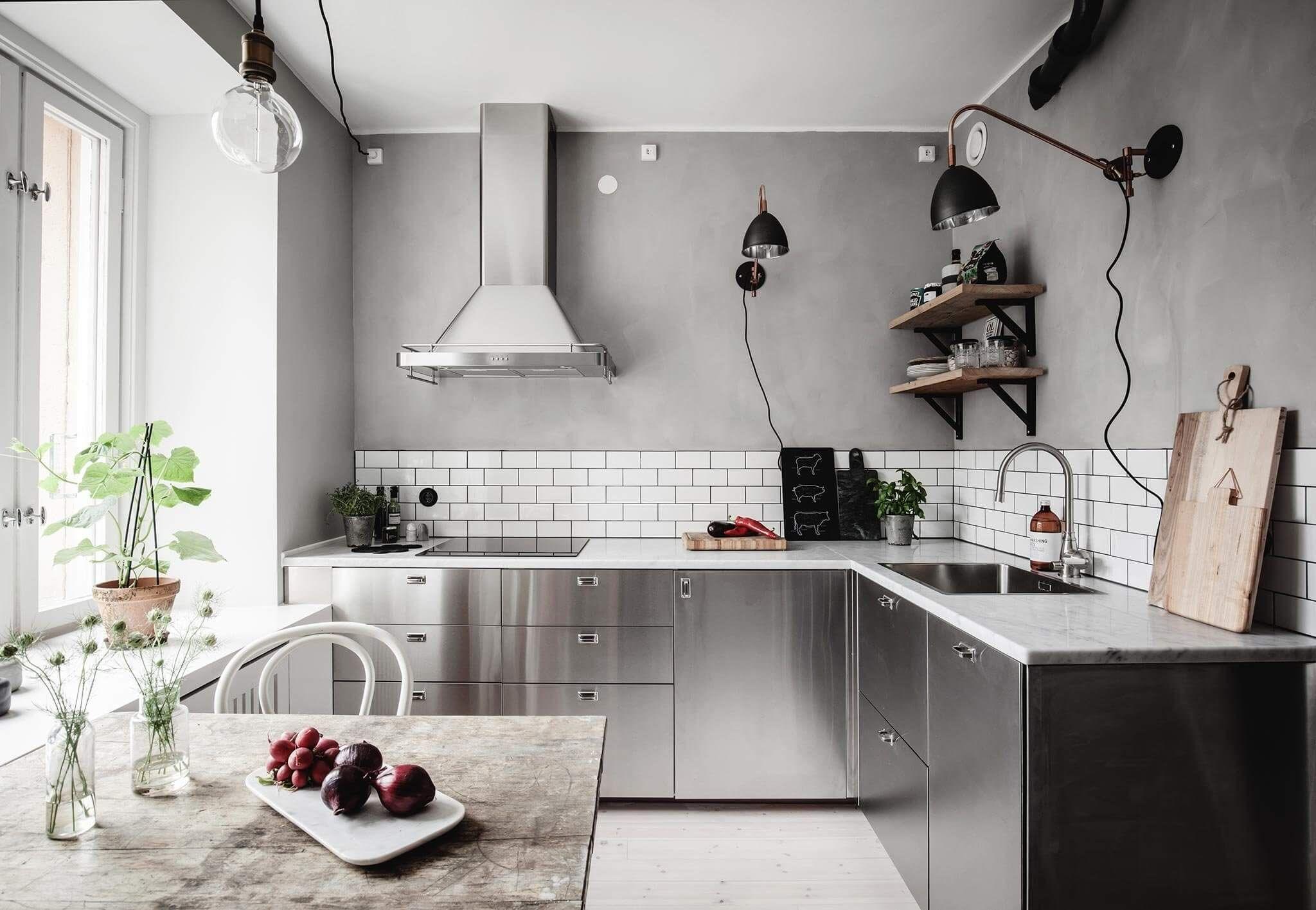 Nesta cozinha escandinava o inox se incorpora ao cimento queimado e tampos de mármore para trazer mais aconchego.