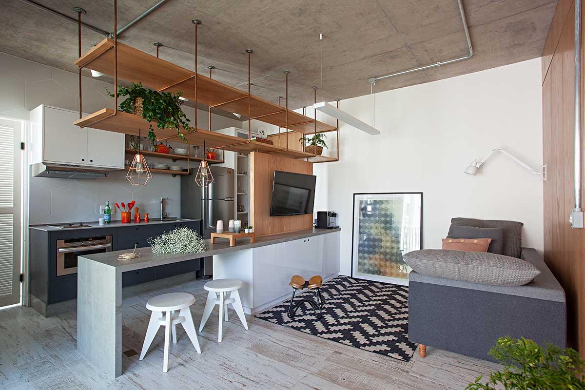 Cozinha escandinava com piso em madeira, iluminaçãoa aprente dando um toque industrial e prateleiras e luminárias em cobre.