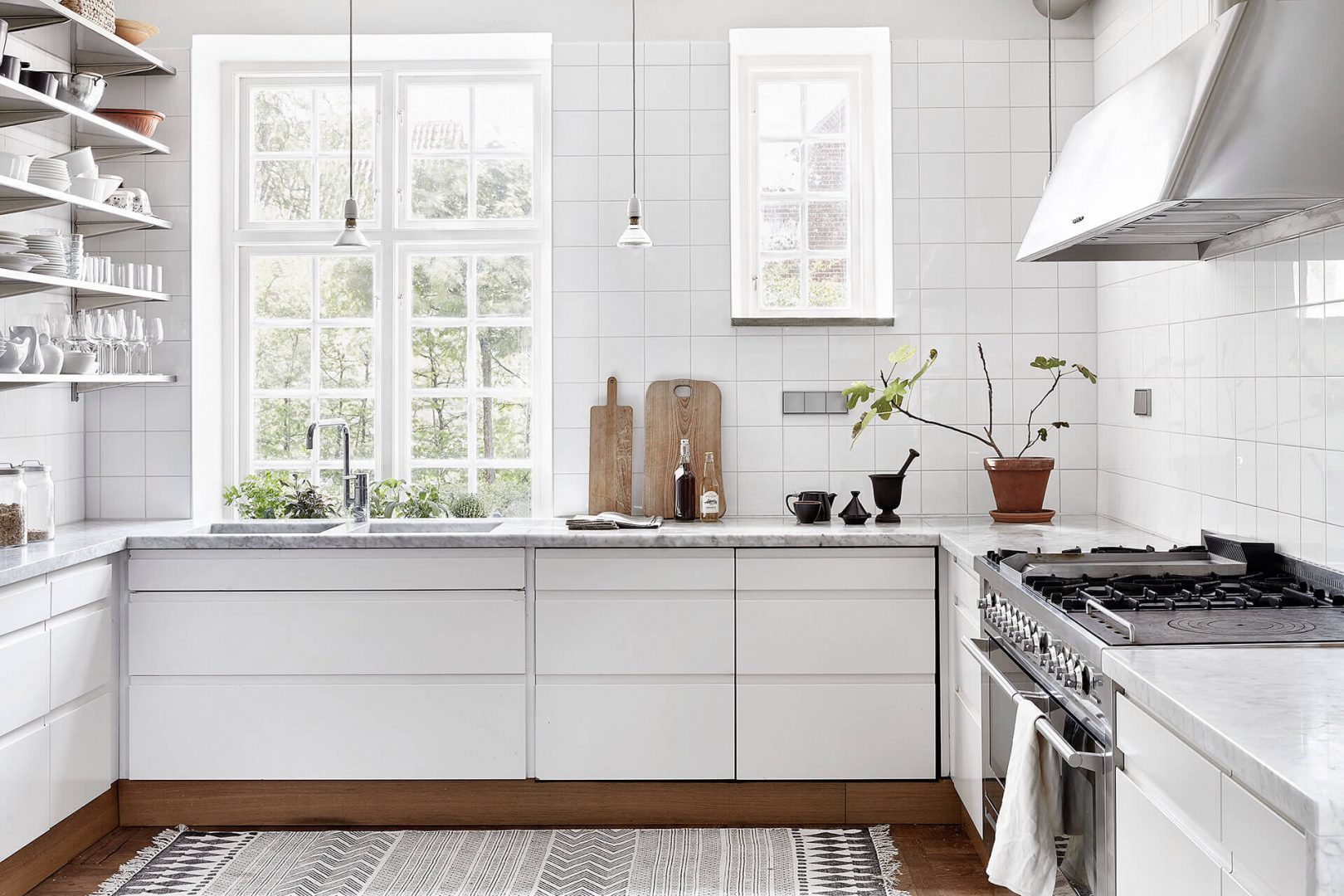 Cozinha escandinava toda em branco, bancada de mármore e apenas o piso em madeira.