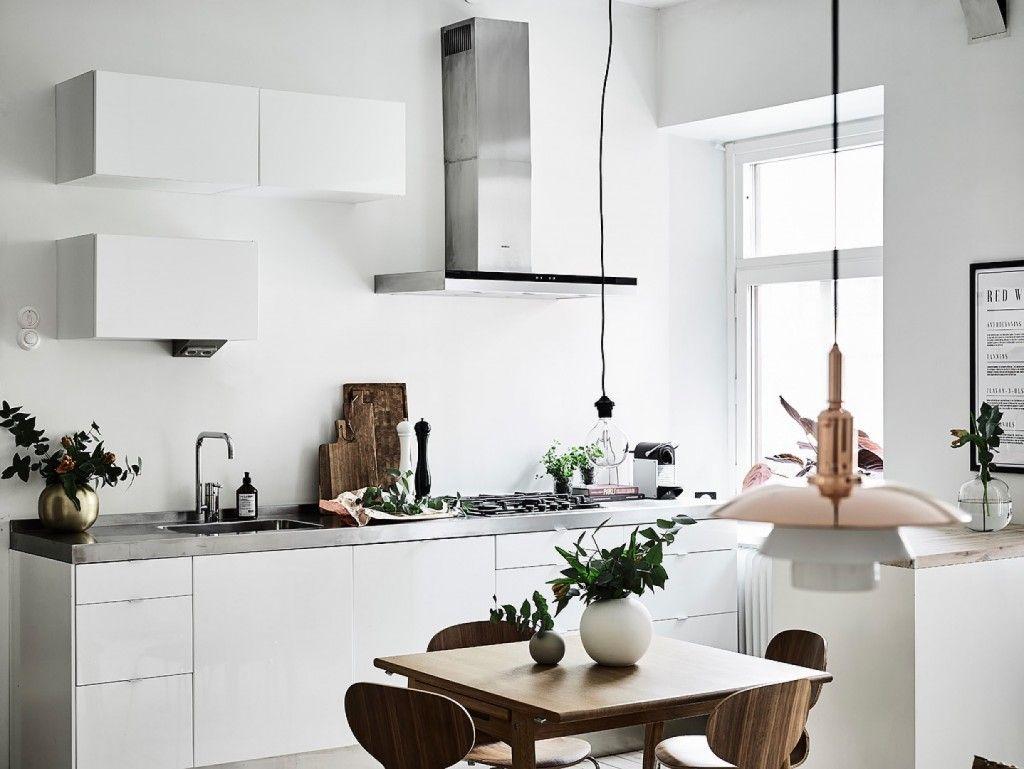 Cozinha escandinava utilizando luminária em cobre, bancada de cimento e mesa com cadeiras em madeira.