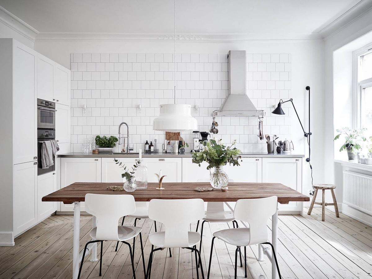 Cozinha escandinava toda em branco combinada ao tampo da mesa em madeira e janelas amplas fornecendo iluminação natural.