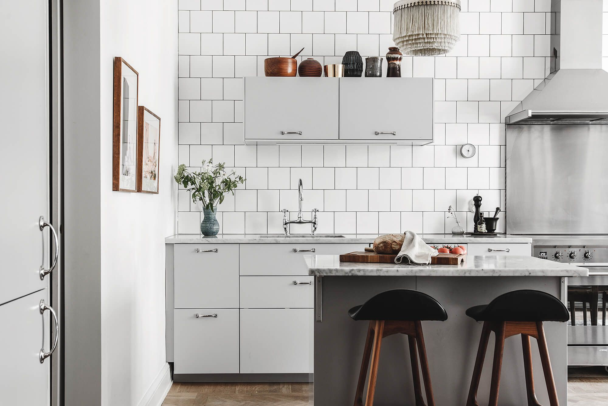 Cozinha escandinava utilizando vários materiais diferentes, azulejo, mármore, madeira, metal, tudo em tons claros pontuados com o preto das banquetas,