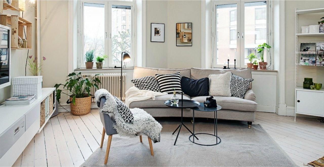 O piso de madeira clara, os tons de bege e móveis brancos com almofadas estampadas criam um ambiente aconchegante.