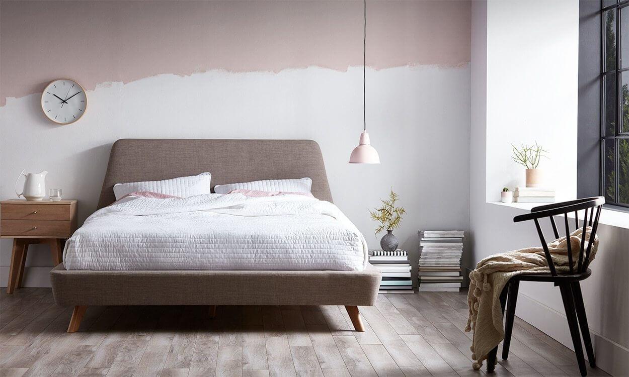 O quarto segue a arrumação bem despojada com livros no chão, pintura descascada na parede e luminária de metal pendente, características do estilo escandinavo.