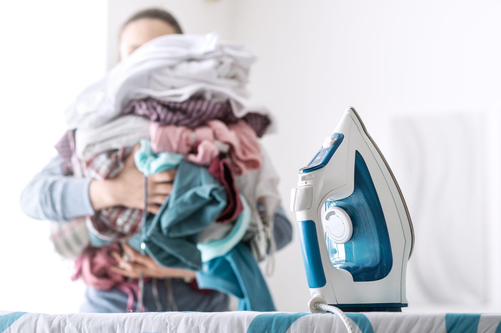 tarefas dome'sticas: mulher com pilha de roupa para passar