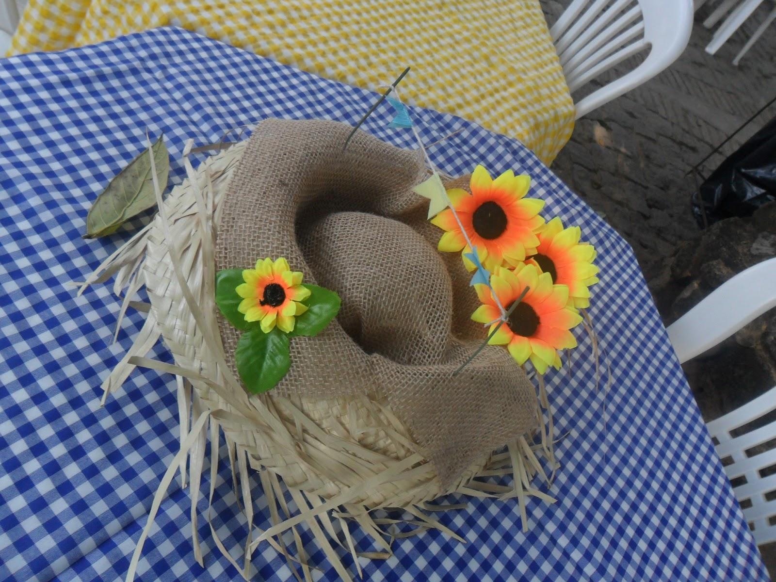 O típico chapéu de palha pode ser decorado com juta e flores e virar um indo enfeite de festa junina de mesa.