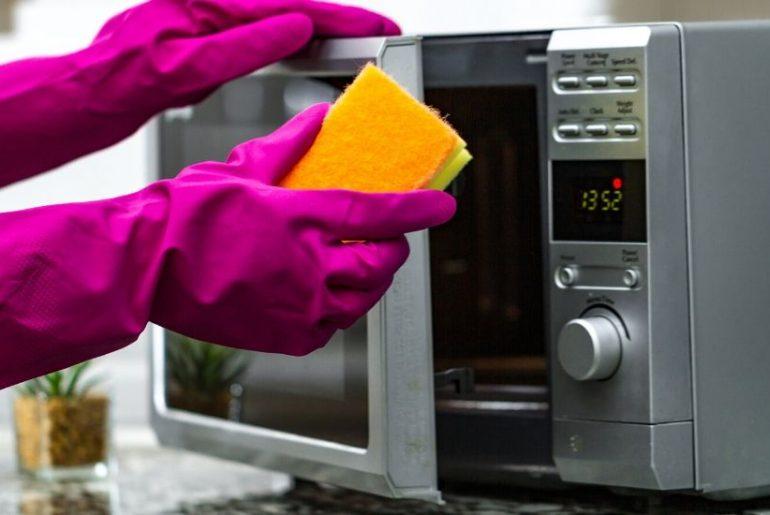 moça mostrando como limpar microondas
